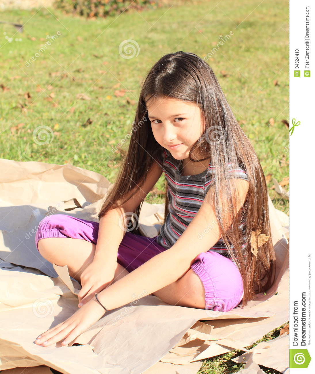 ... kid - smiling girl with long brown hair cutting big leaves of paper