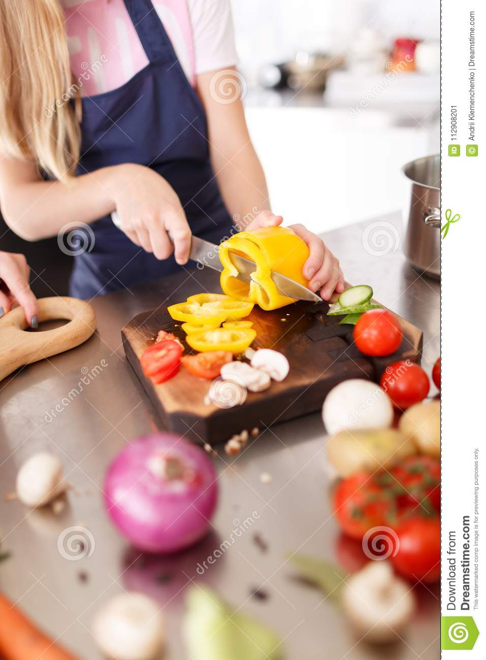 A Girl Cutting Vegetables For The Salad On A Wooden Desk In The