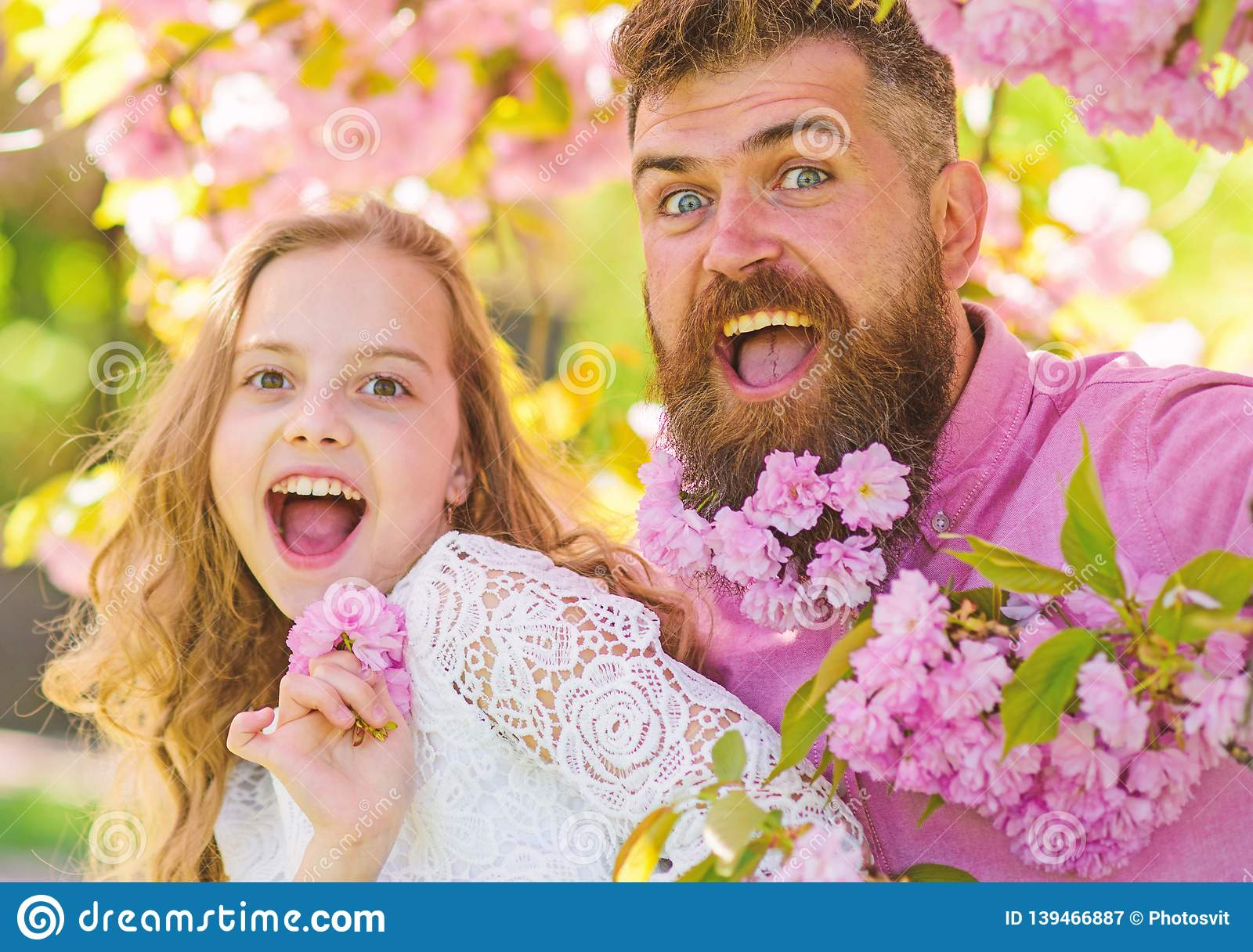 Girl with dad near sakura flowers on spring day. Father and daughter on happy faces play with flowers and hugs, sakura