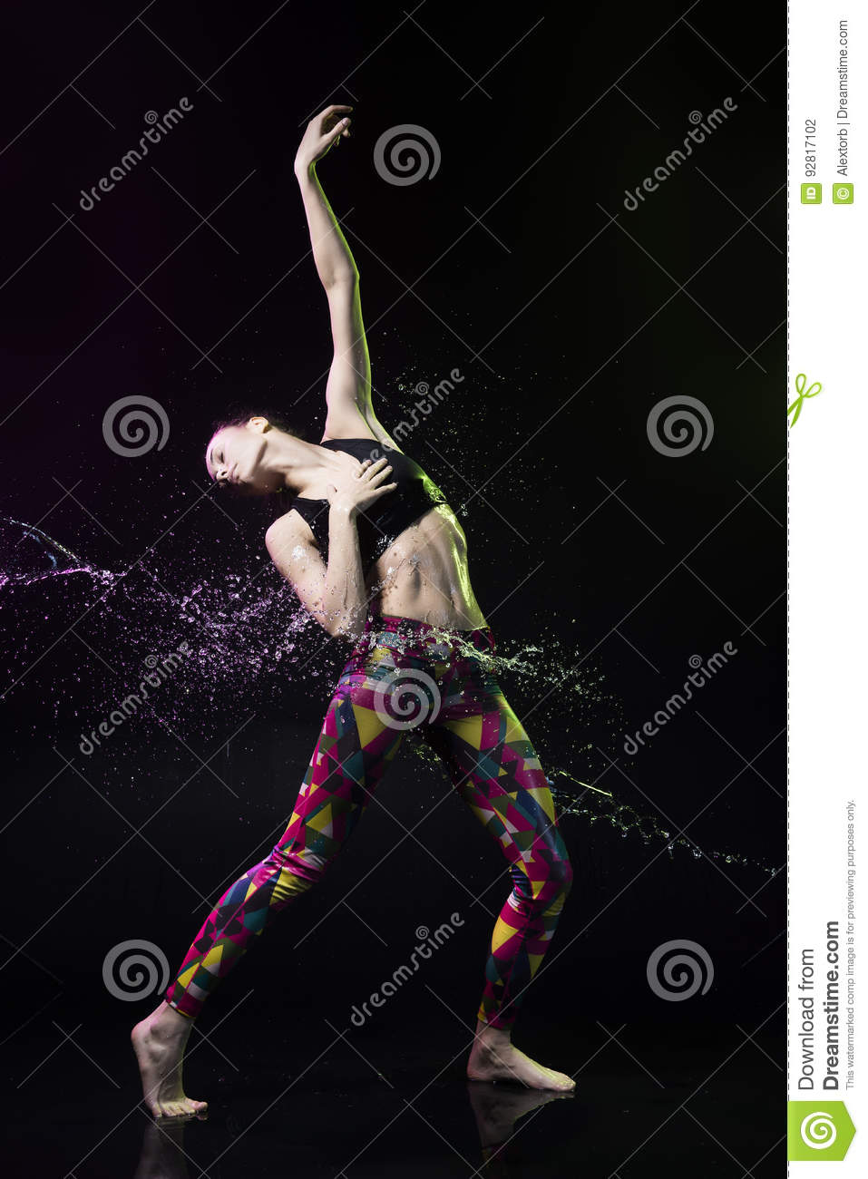 The girl dances on the floor covered with water on a black background and water splashes around her