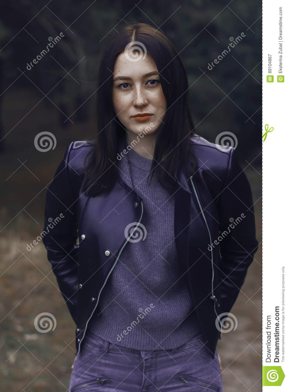 fc3b1511e357d Girl with dark hair in the forest. She wears a black leather jacket and  gray jeans. A woman of model appearance stylishly dressed.