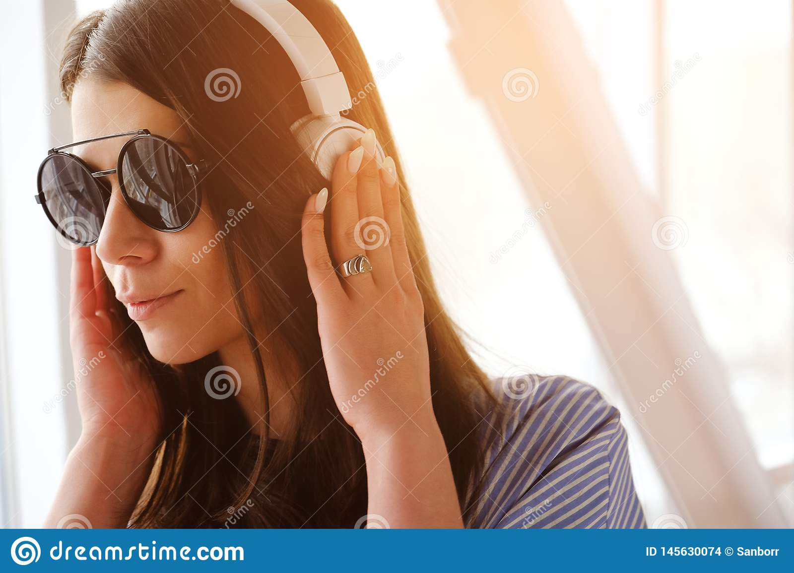 A girl with dark hair in headphones listening to music, sitting in a room, airport, office. A young woman with glasses