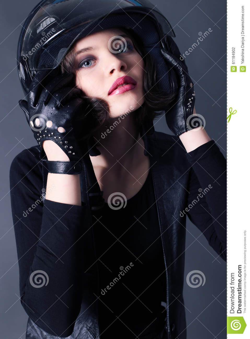 girl with dark short hair wears biker clothes leather jacket and helmet
