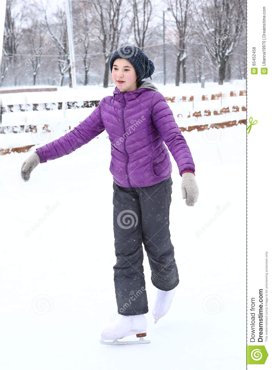 Girl in dawn jacket skating on the ice rink