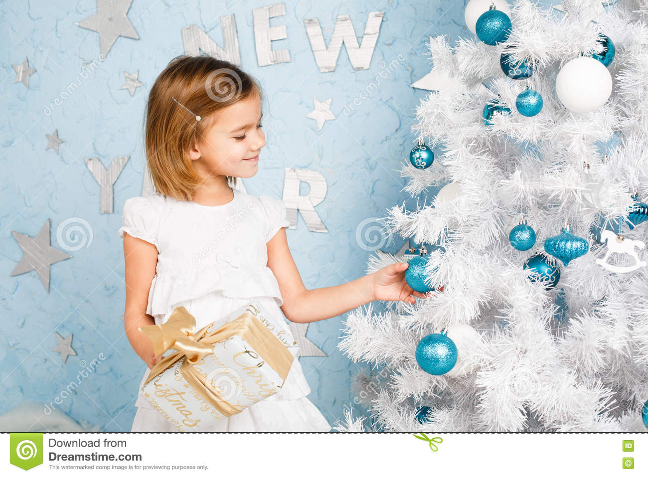 Girl decorates the Christmas tree balls and smiling