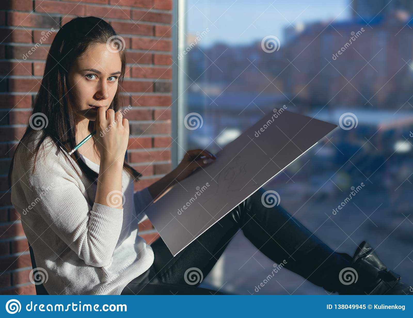 Girl designer sitting on a chair by the window and draws a sketch works as an artist