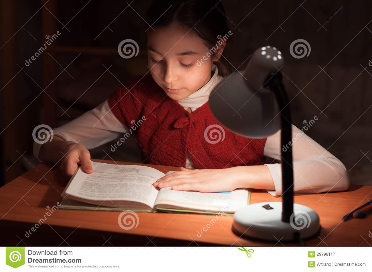 Girl At Desk Reading A Book By Light Of The Lamp Royalty