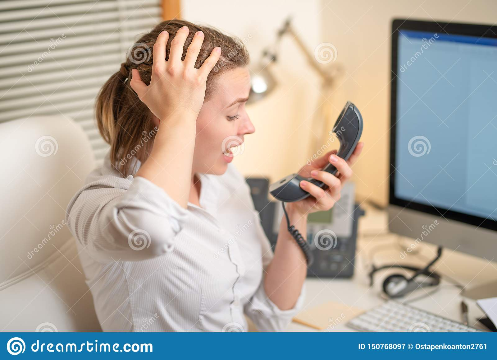 Girl dispatcher shouts working with the phone. In the call center, angry. evil