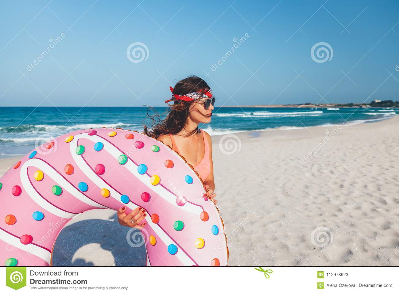 Girl with donut lilo on the beach