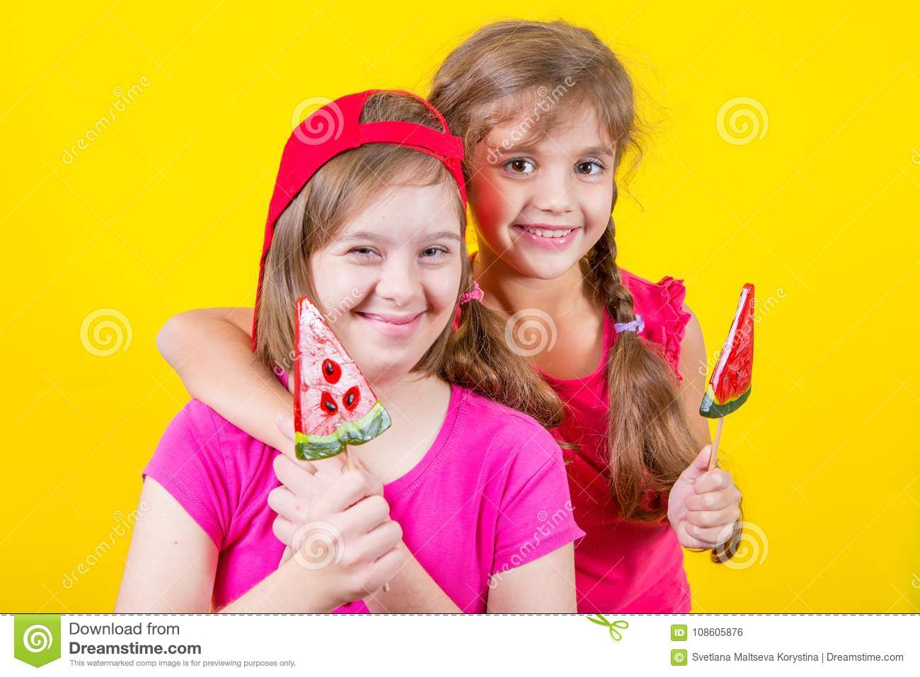 Girl Down syndrome and little girl with large Lollipop