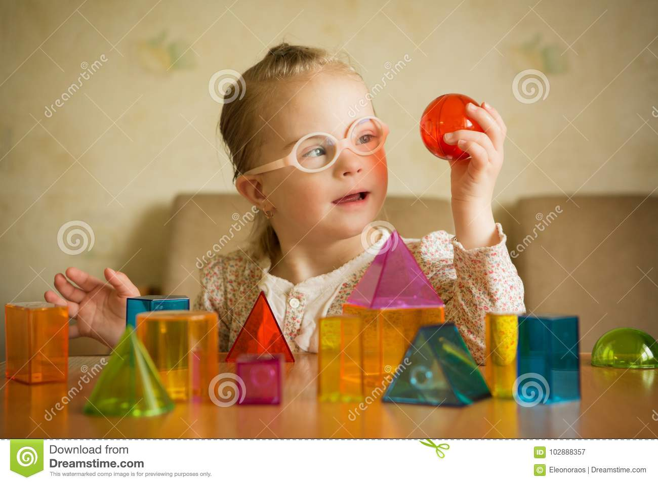 Girl with Down syndrome playing with geometrical shapes