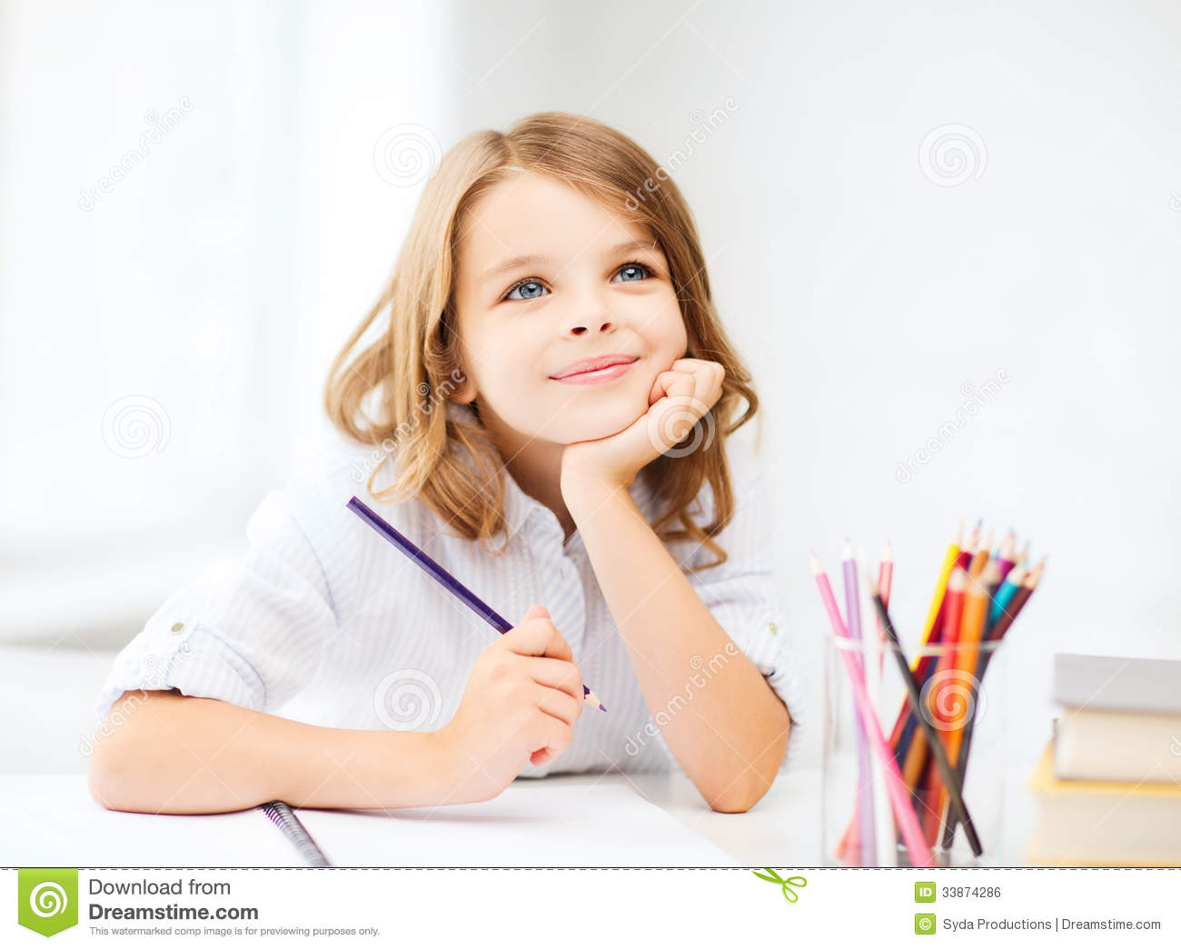 Girl drawing with pencils at school
