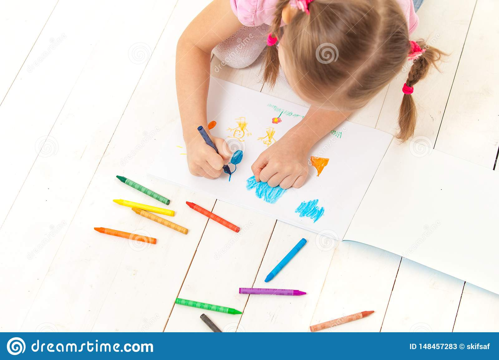 The girl draws with crayons in the album