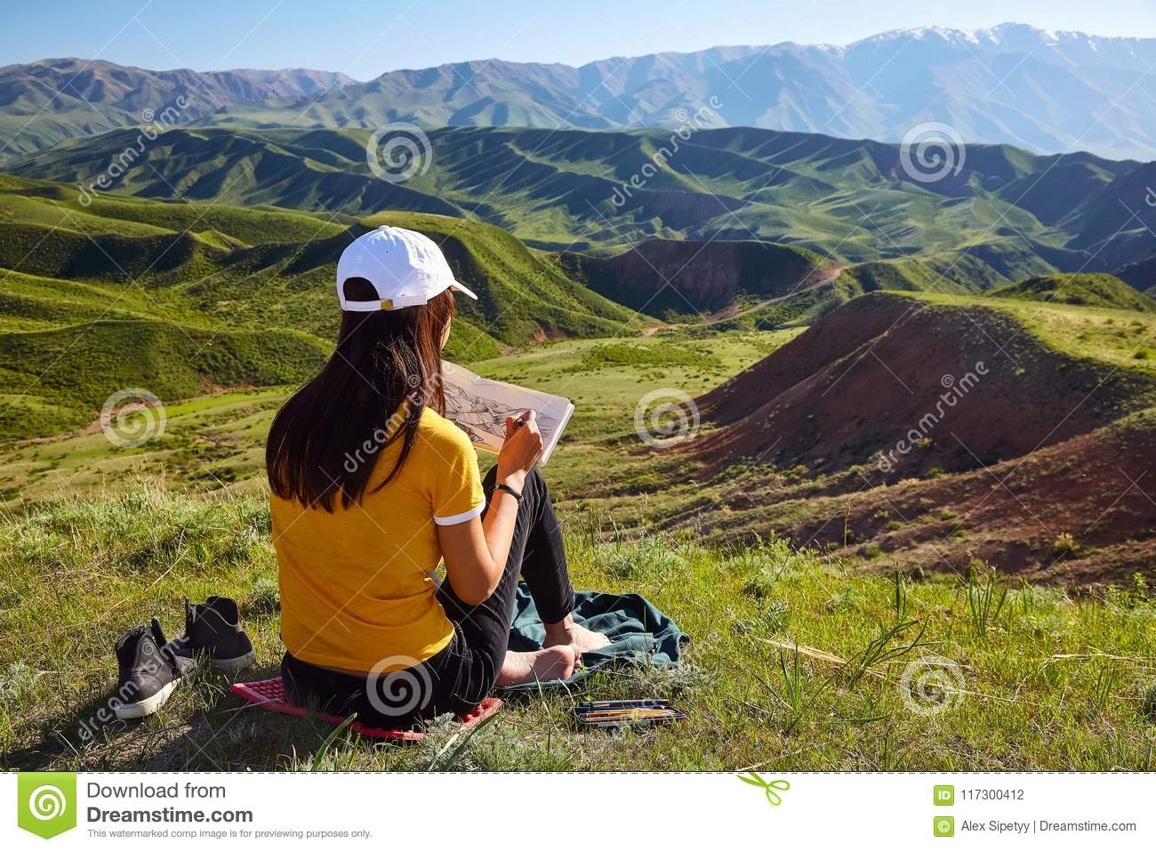 Girl draws on nature spring landscape. Painting outdoors. Kazakh