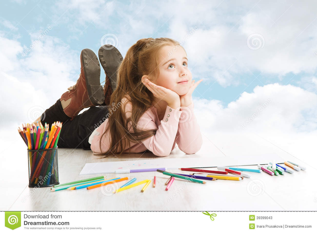 Girl dreaming, looking for drawing idea. Smiling child lying over blue ...