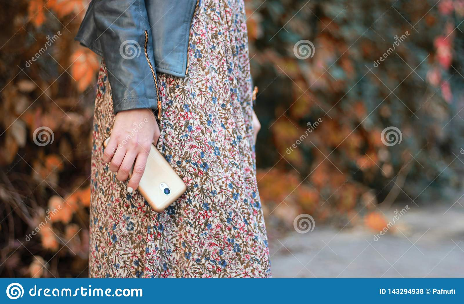Girl in the dress holds the phone