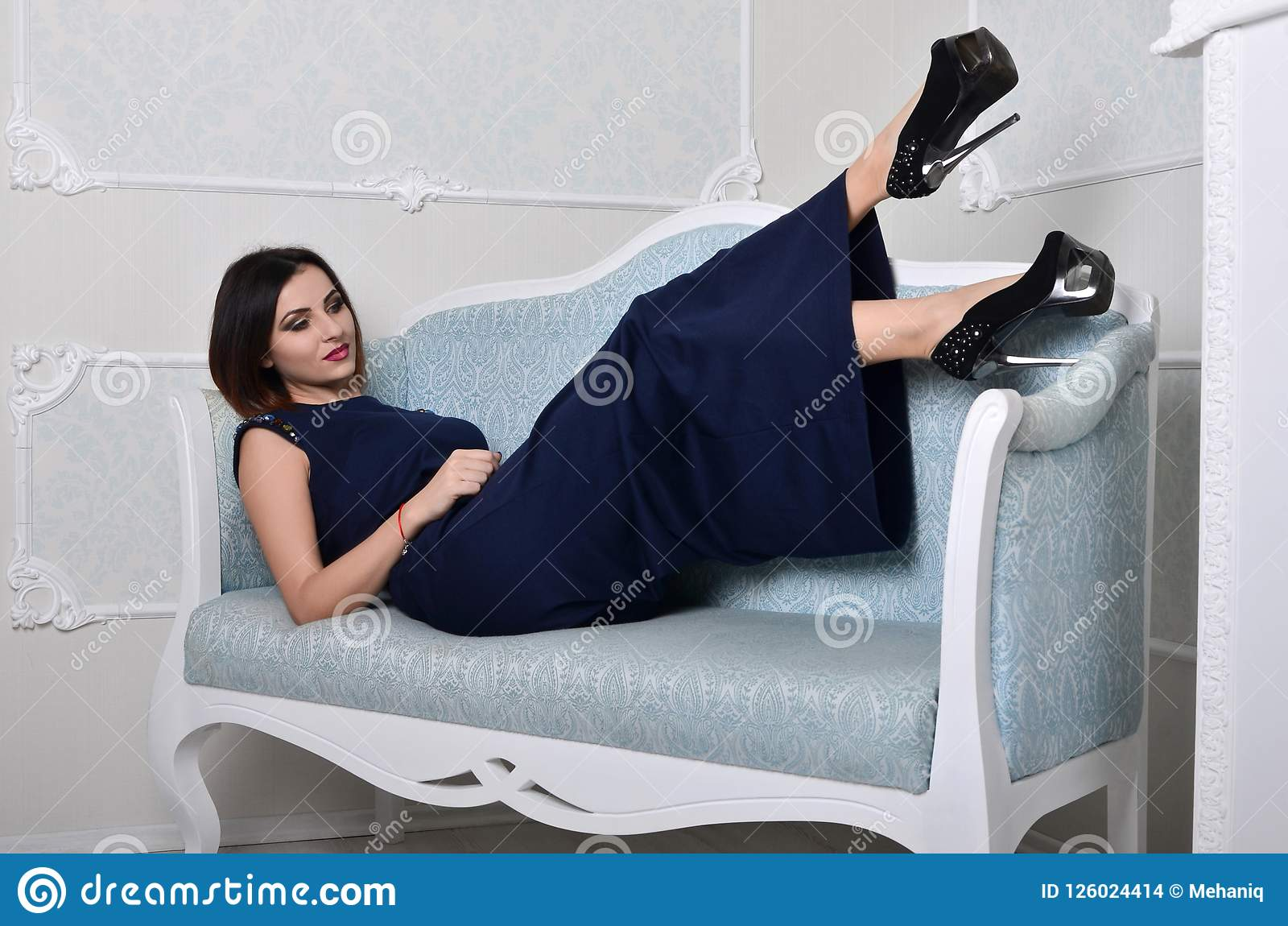 The girl in a dress lies on a blue sofa