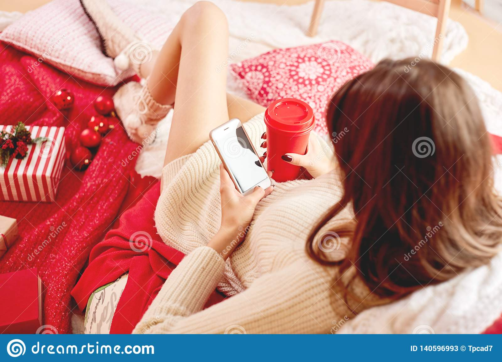 Girl dressed knitted dress and knitted socks lies on red-white blankets and pillows and holds a mobile phone and red cup