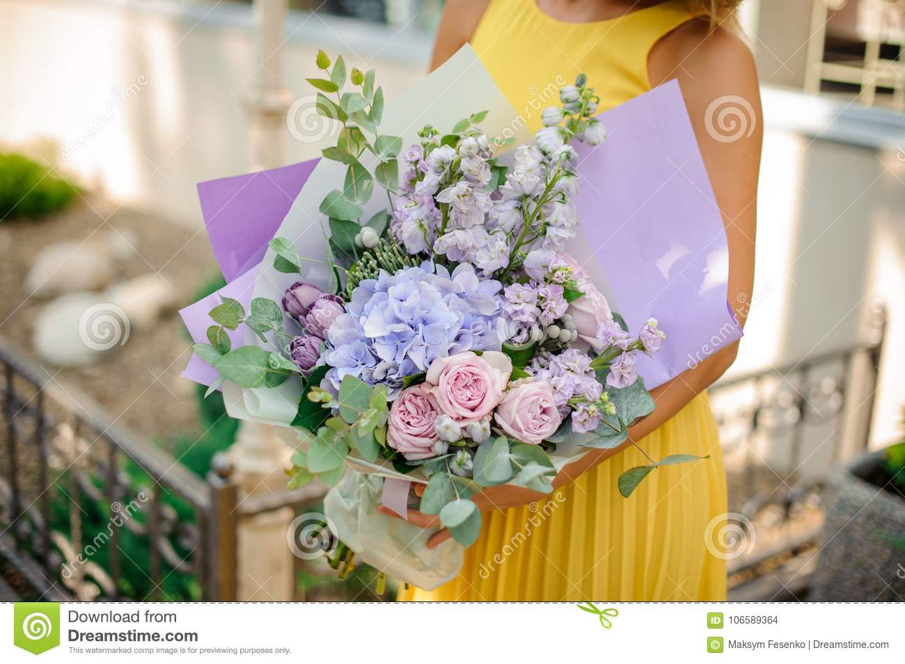 Girl dressed in a yellow dress holding a purple bouquet of flowers download girl dressed in a yellow dress holding a purple bouquet of flowers stock photo mightylinksfo