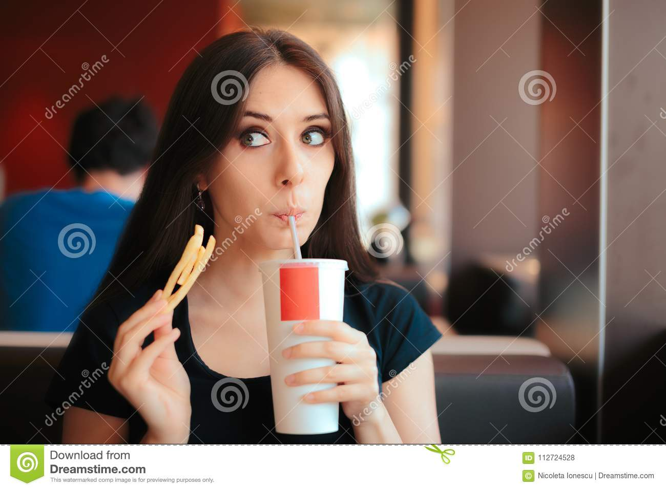 Girl Drinking Soda and Eating Fries in Fast Food Restaurant