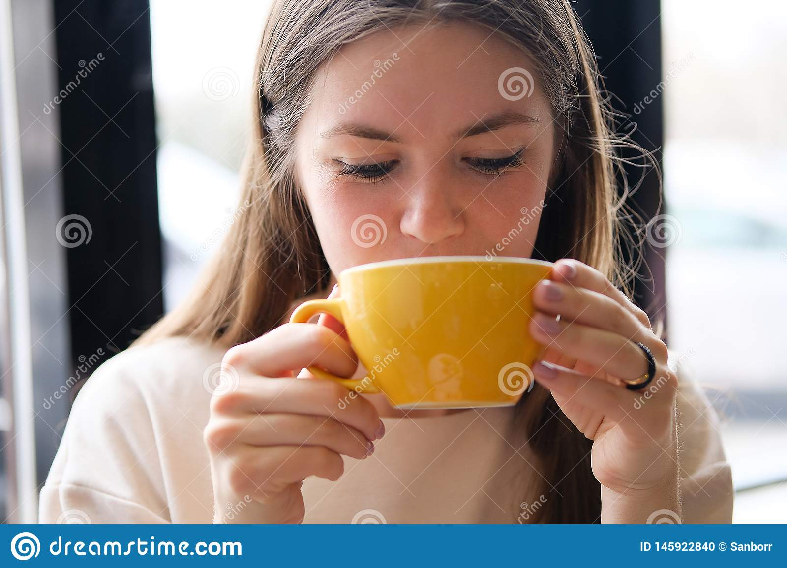 The girl drinks coffee from a yellow mug, looking down. Young beautiful woman sitting in a cafe, holding a Cup of cappuccino.