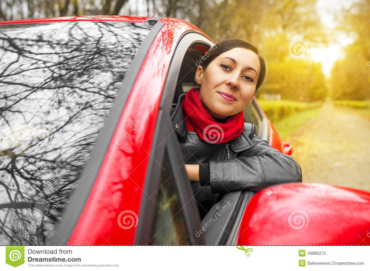 Girl driving a red car.