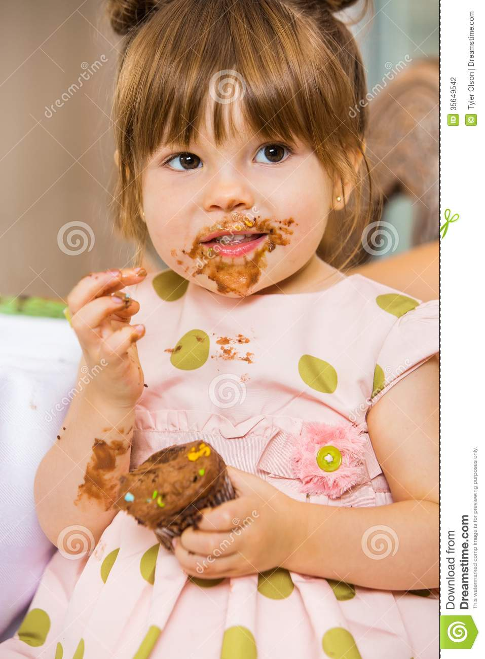 Girl Eating Birthday Cake With Icing On Her Face Stock