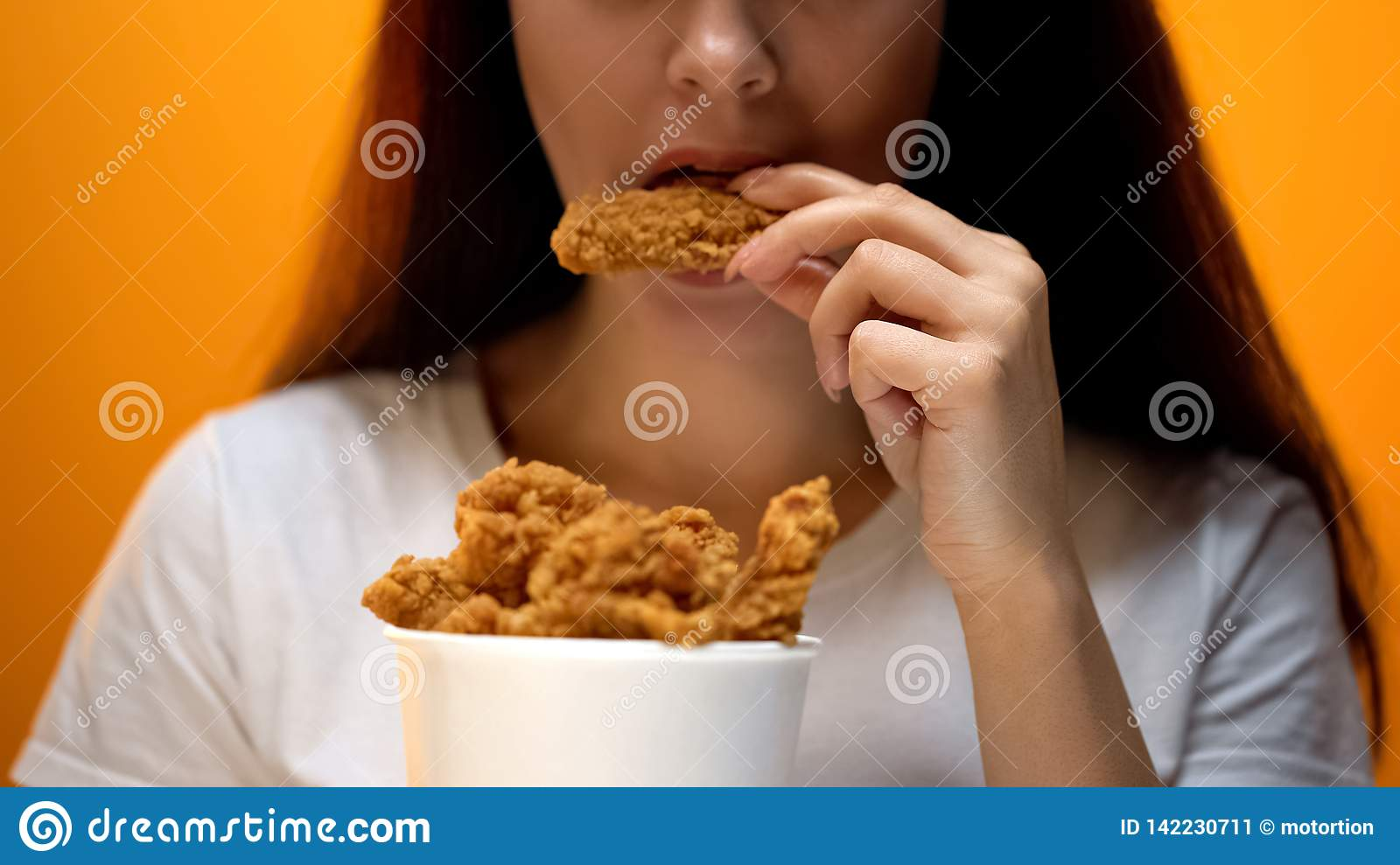 Girl eating chicken wings, high calorie food and health risks, cholesterol