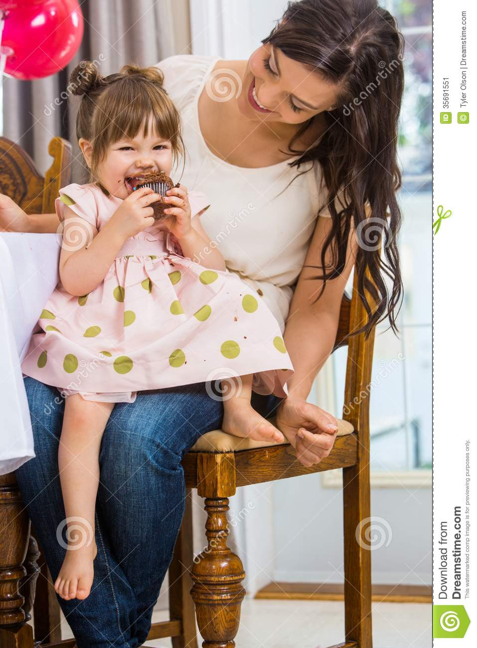 Girl Eating Cupcake While Sitting On Mother S Lap Stock