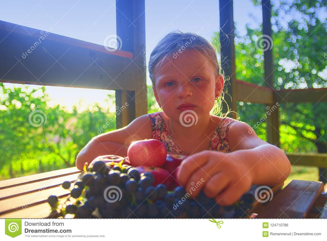 Girl is eating fruits. Apples and grapes on a table. The little girl is sitting at a table on a verandah and eati