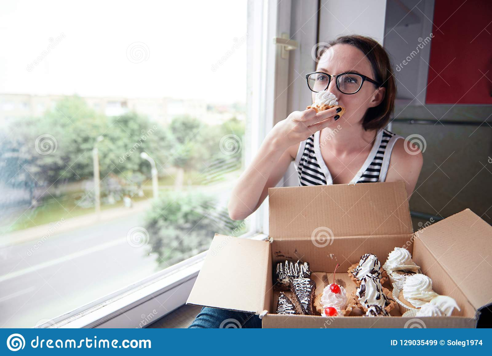 Girl eating tasty cakes, sitting by the window, sweet food and pleasure