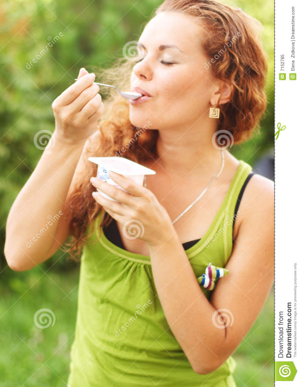 Girl eats yogurt and has closed eye from pleasure