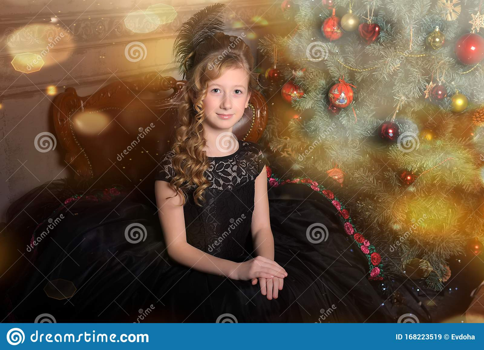 Girl In Elegant Black Dress With A Feather In The Evening Hairstyle By The Christmas Tree Stock Image Image Of Carnival Dress 168223519