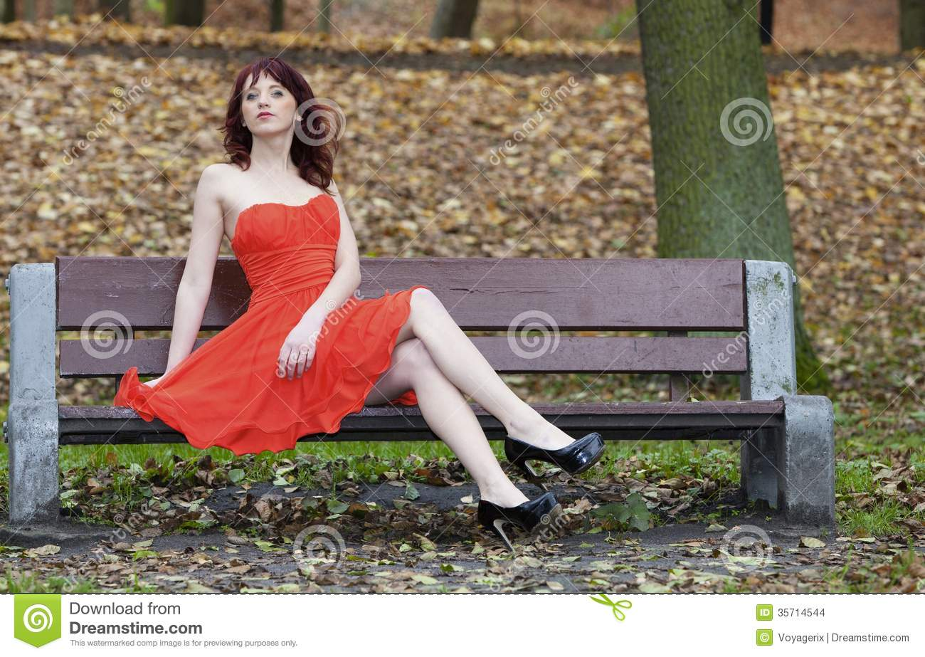 girl in elegant red dress sitting on bench in autumnal