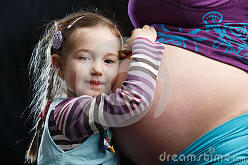 Girl embracing pregnant mother