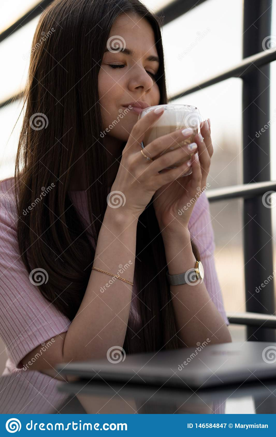The girl is enjoying coffee. A cup of coffee in female hands. On the table is a closed laptop