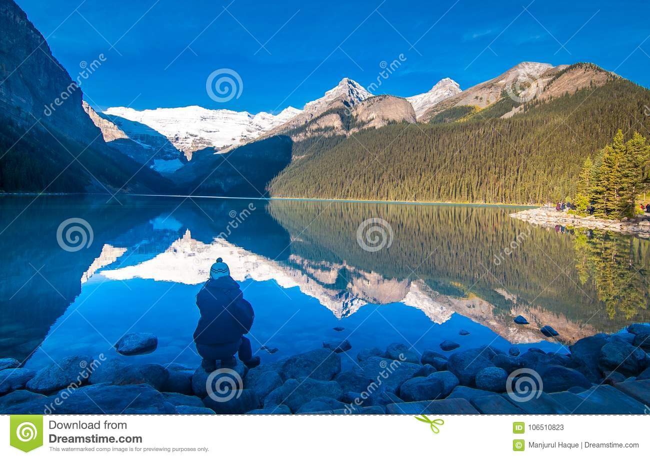 Girl enjoying the reflection of snowy mountain and evergreen tree in the water of lake Louise