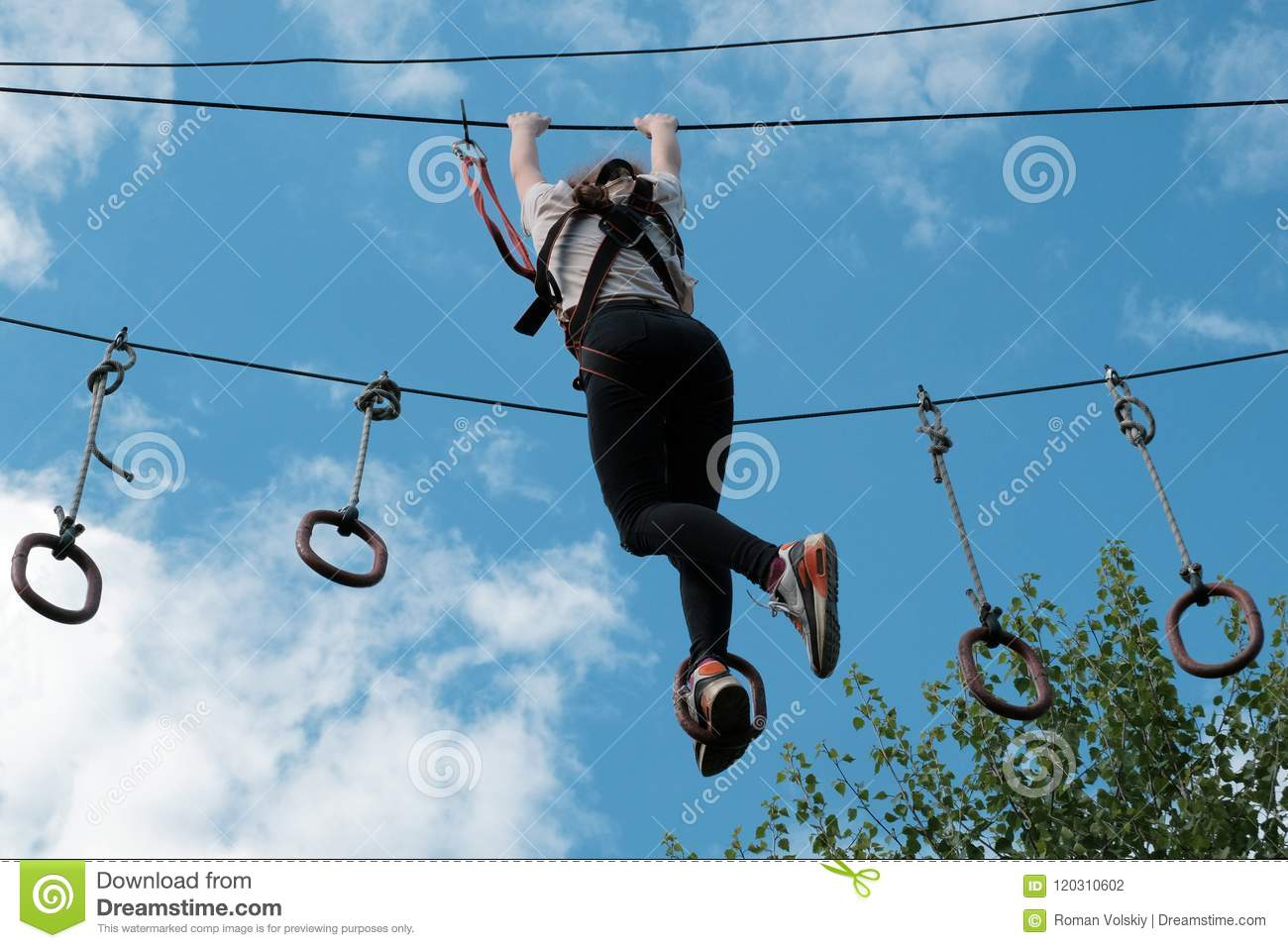 A girl enjoys climbing in the ropes course adventure. Climbing high wire park. Copy space for your text.