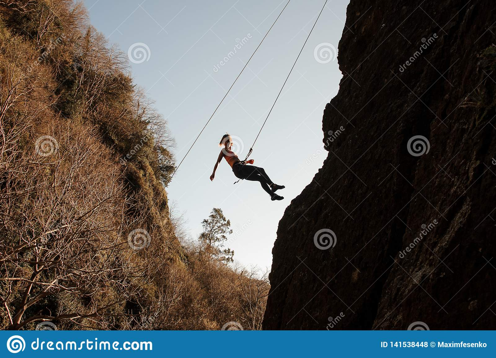 Girl equipped with a rope abseiling on the sloping rock and looking down