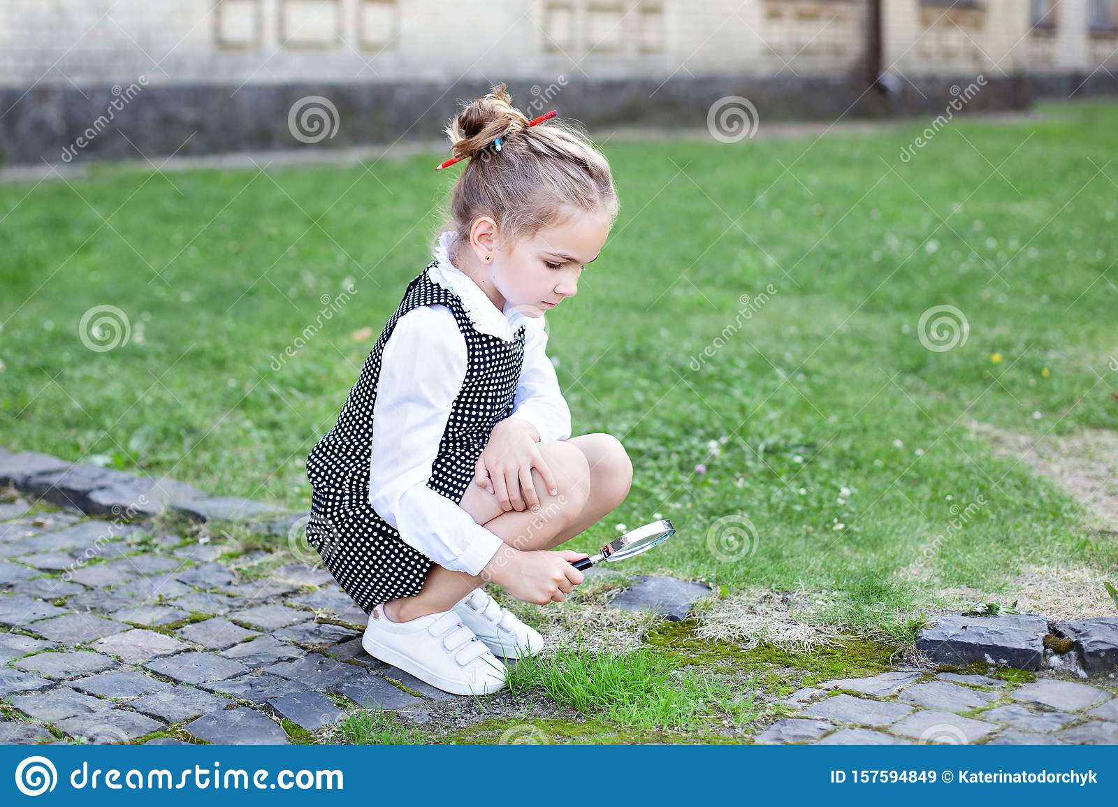 Girl exploring nature in a meadow with a magnifying glass looking at insects. Back to school. Education Concept. Preschool Educati