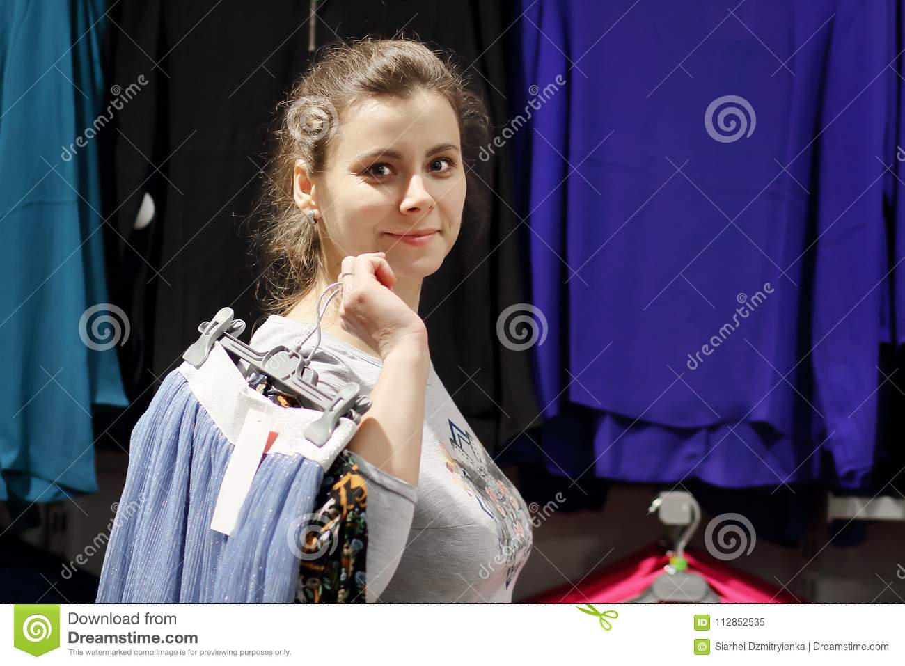 Girl in fashion boutique got clothes and goes to dressing room. Shopping concept. Attractive young woman chooses clothes in store