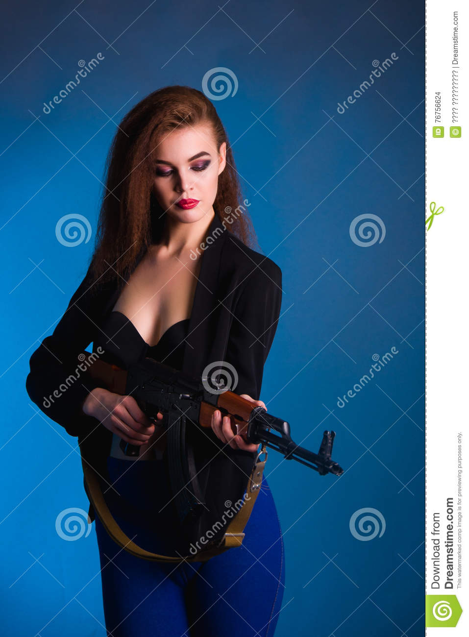 Girl fashion photography in the studio with a gun is dangerous