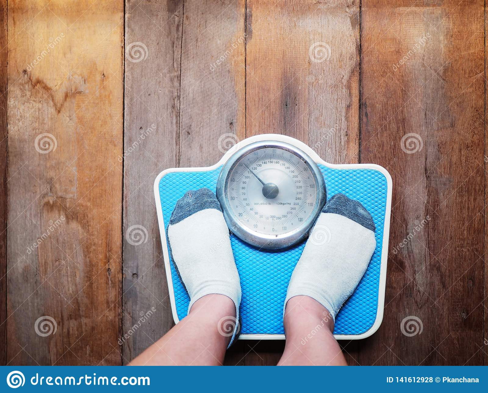 Girl feet standing on weight scale