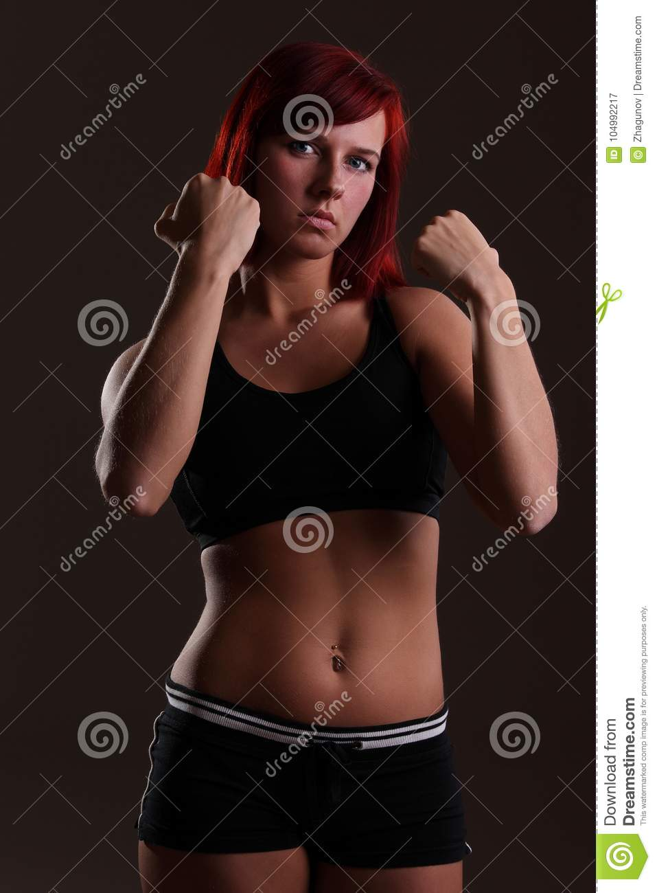Young strong woman on a dark background