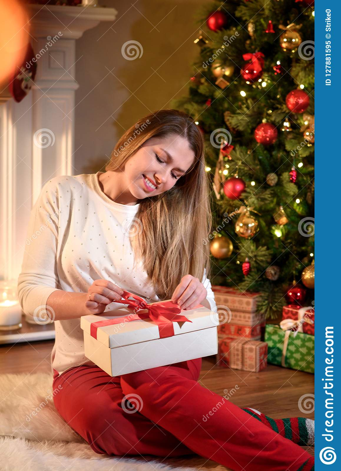Girl fixing a ribbon on new year gift box smiling