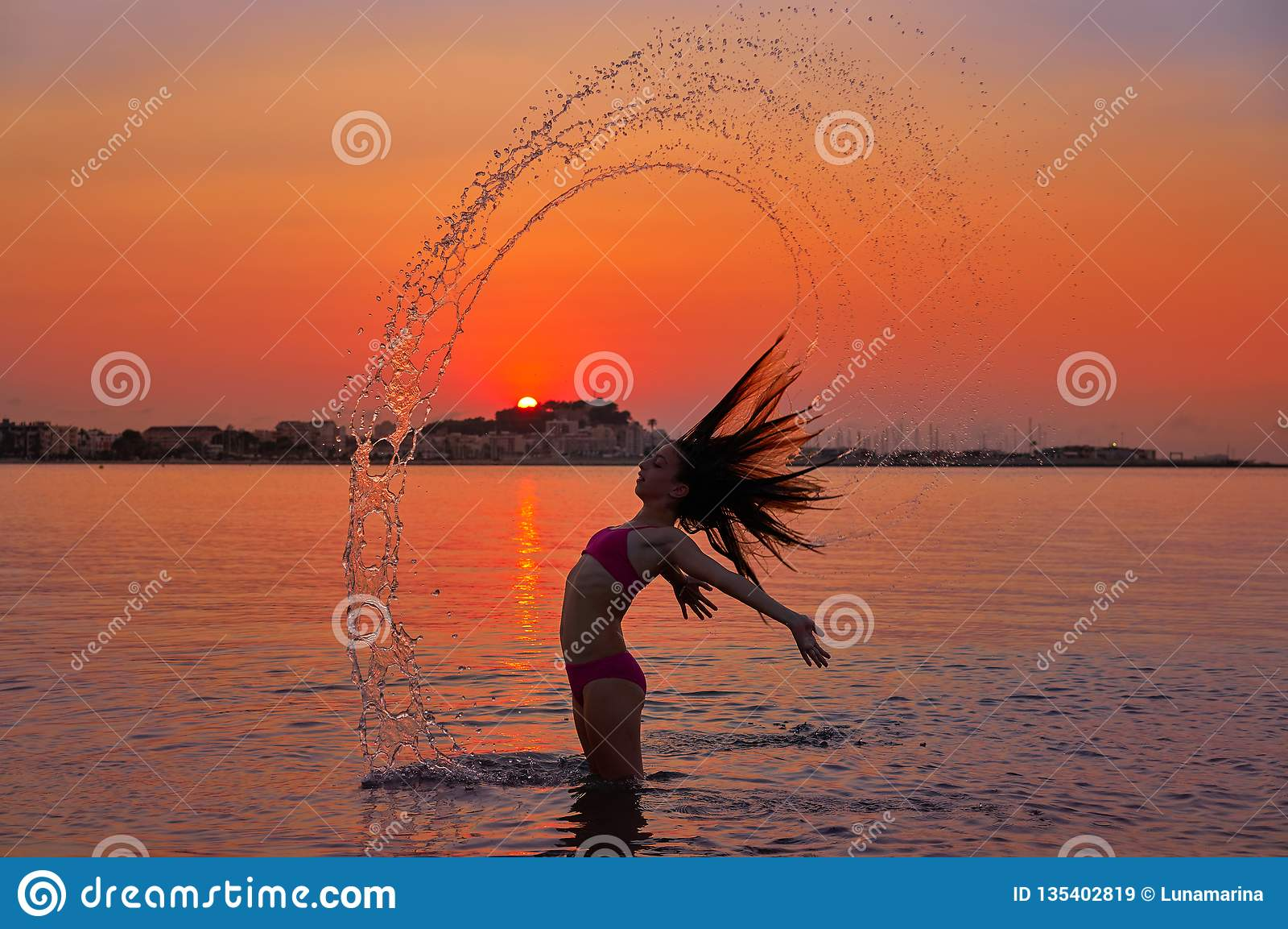 Girl flipping hair flip at sunset beach