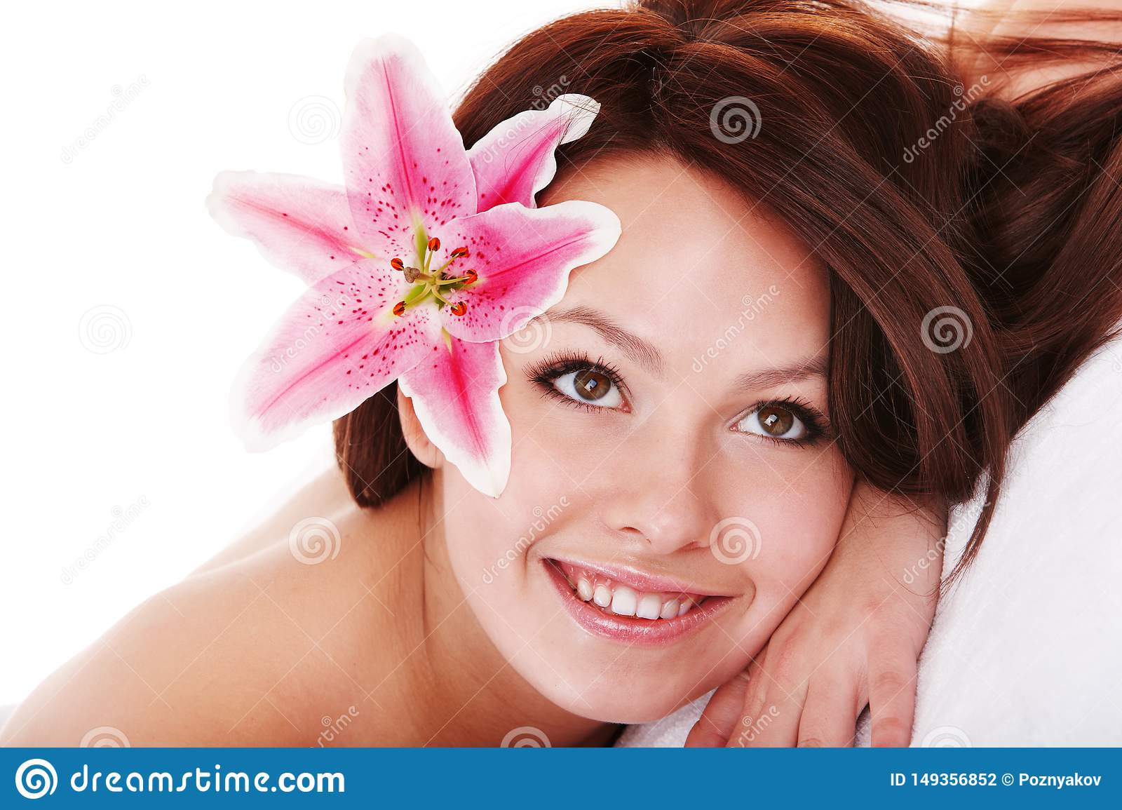 Girl with flower in hair on massge in spa salon .