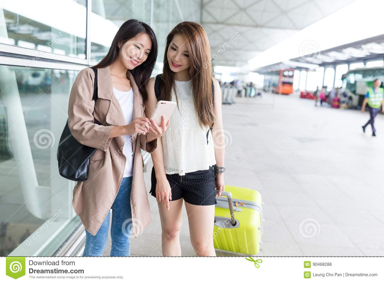 Girl friends use of cellphone at international airport