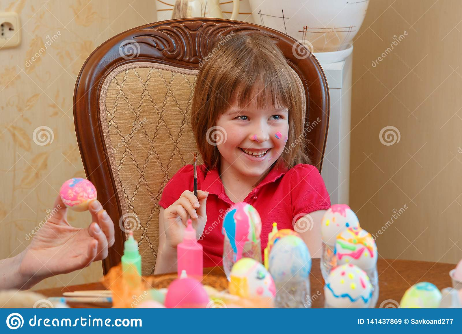 The girl is fun painting eggs for Easter