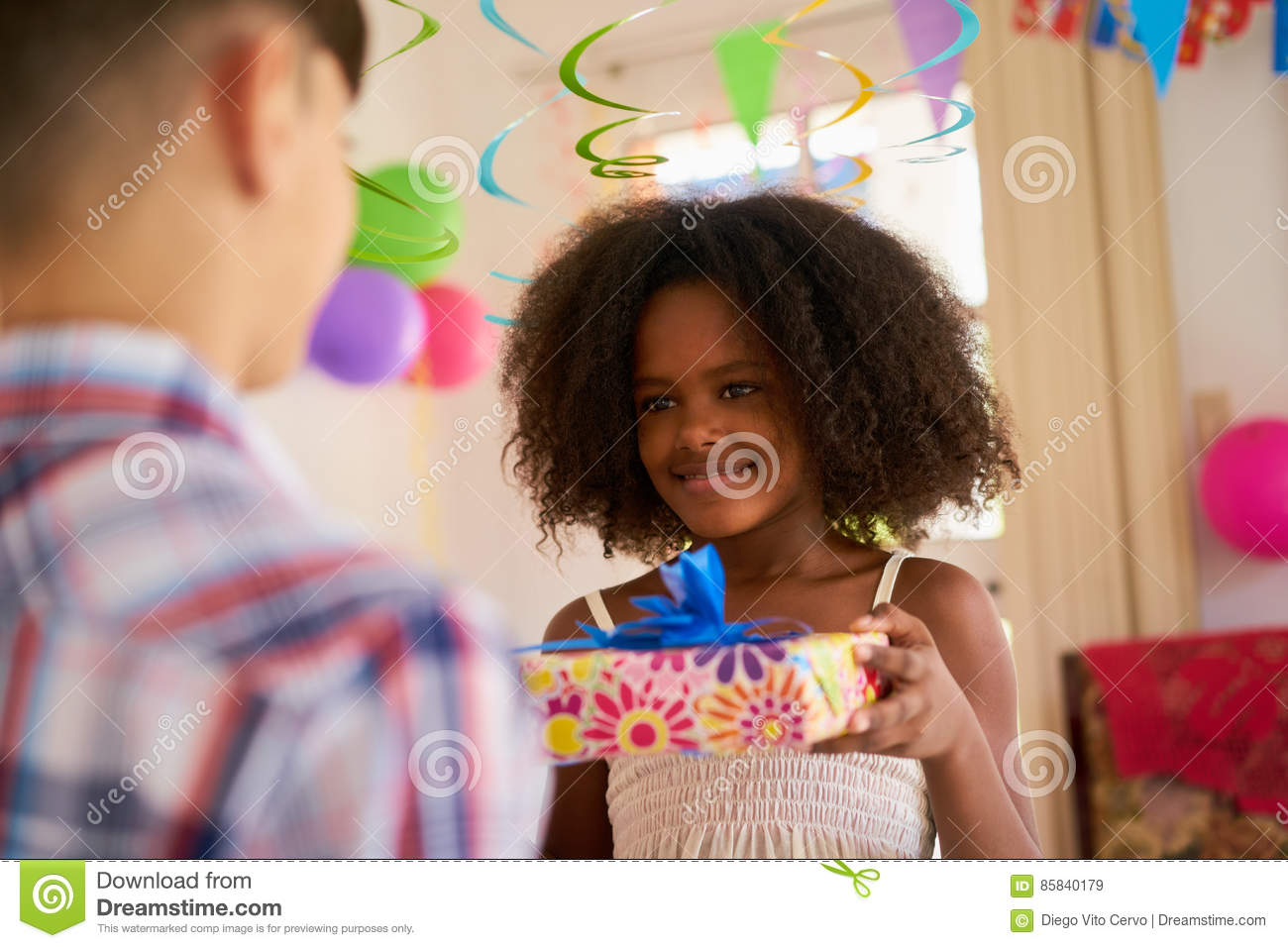 Group Of Happy Children Celebrating Birthday At Home Kids Having Fun Party Cute Black Girl Giving Gift Box To Friend